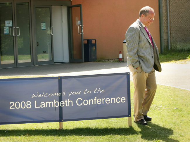Gay American Bishop Gene Robinson walks past a sign near the market stall area of the Lambeth Conference at the University of Kent on July 21, 2008 in Canterbury, England.