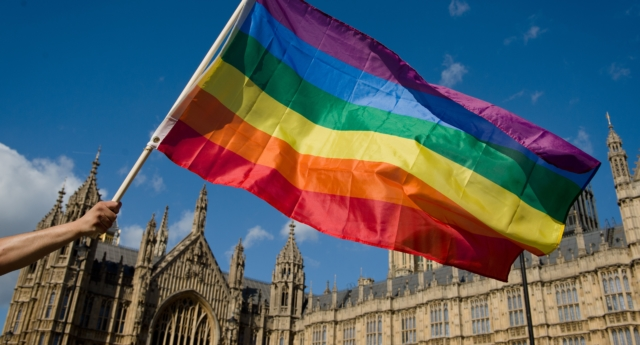 A protester holds a rainbow flag outside the Houses of Parliament in central London on June 3, 2013 (Getty)