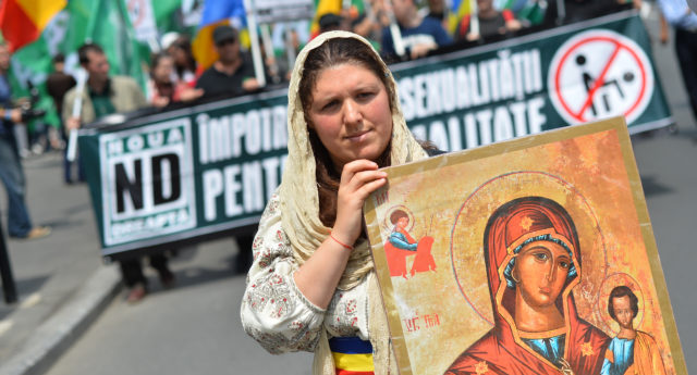A Romanian woman holds an Orthodox icon as she marches with Romanian flag during a protest against incoming Gay Pride in Bucharest on June 8, 2013. (Daniel Mihailescu/AFP/Getty)