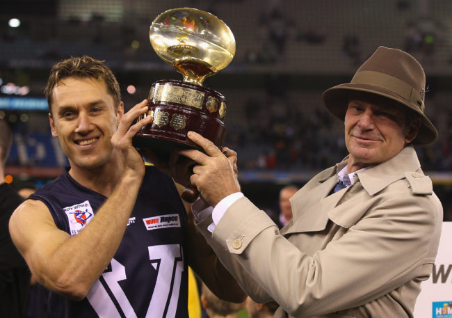 Sam Newman lifts trophy at the Etihad Stadium in Melbourne, Australia
