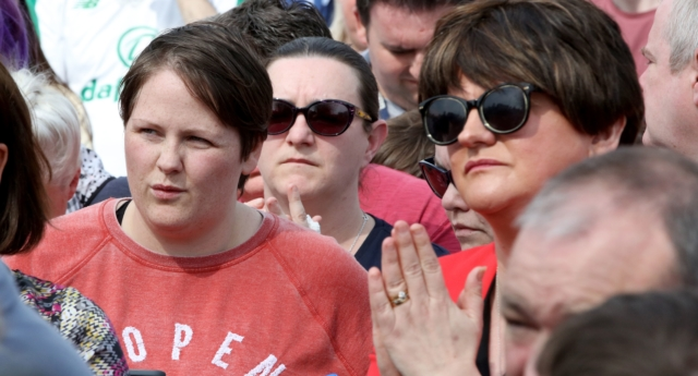 Sara Canning (L), partner of killed journalist Lyra McKee, stands beside Democratic Unionist Party (DUP) leader Arlene Foster (R) at a gathering to condemn McKee's killing near the scene of rioting violence in the Creggan area of Derry in Northern Ireland on April 19, 2019. (PAUL FAITH/AFP/Getty)
