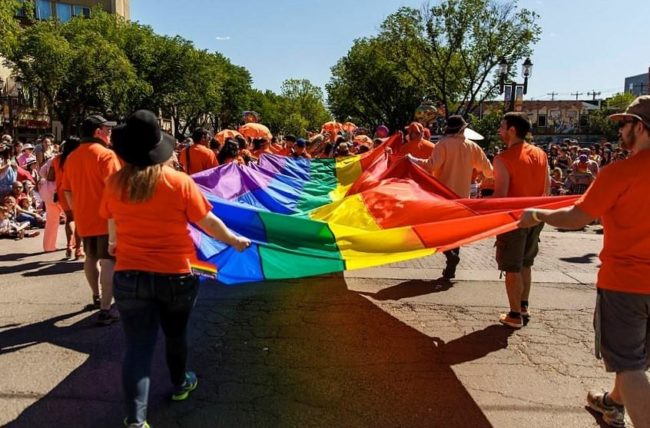 People carrying a rainbow flag at Edmonton Pride