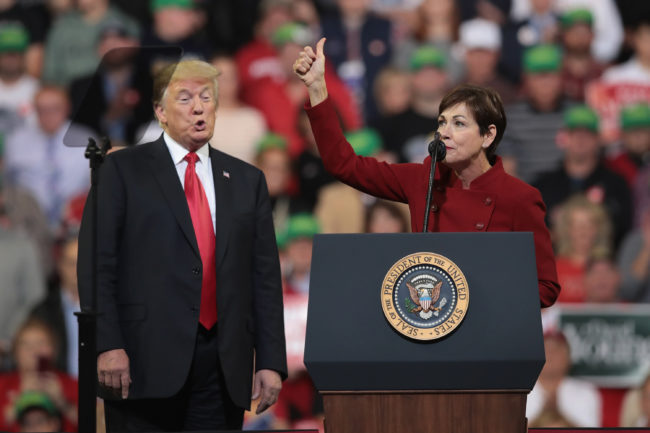 U.S. President Donald Trump listens as Iowa Gov. Kim Reynolds speaks during a campaign rally at the Mid-America Center on October 9, 2018 in Council Bluffs.