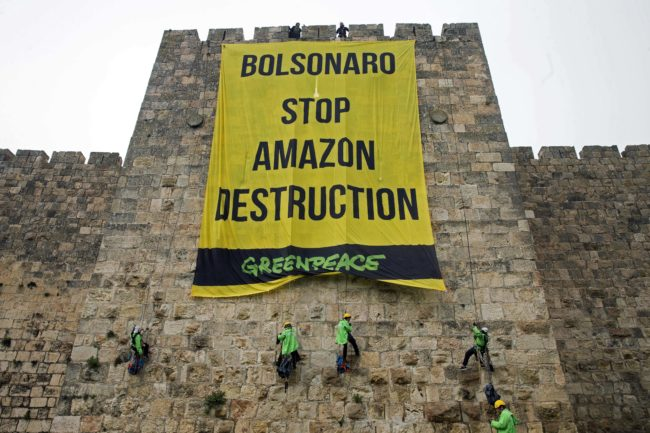 Greenpeace activists hang a large banner on the ramparts of the Old City of Jerusalem with a message to the visiting Brazilian president concerning the Amazon, on April 1, 2019.