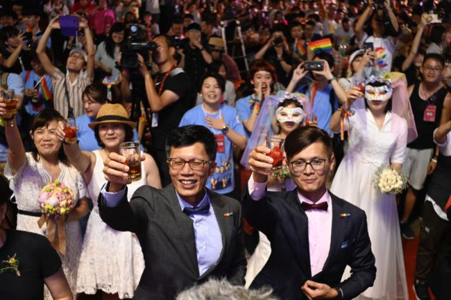 China Taiwan response: A gay couple gesture during a mass wedding banquet in front of the Presidential Palace in Taipei on May 25, 2019.