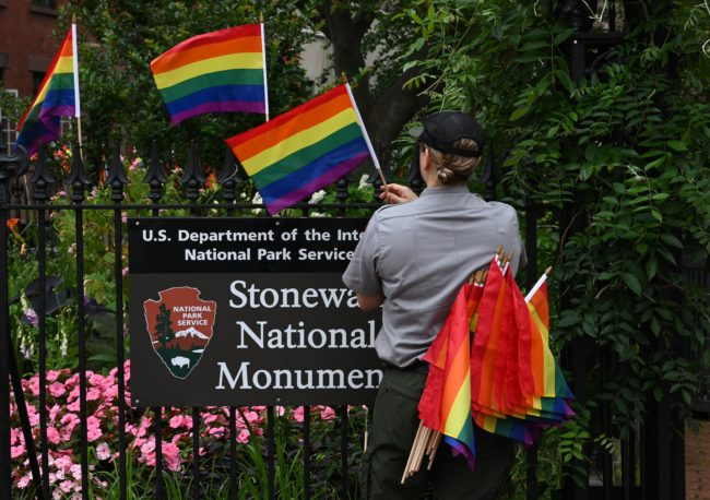 National Park Service rangers places rainbow flags on the fence at the Stonewall National Monument in the West Village neighborhood of Greenwich Village in Lower Manhattan, New York City on June 19, 2019.