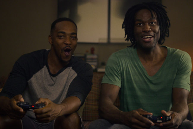 Striking Vipers characters sitting on a sofa playing video games
