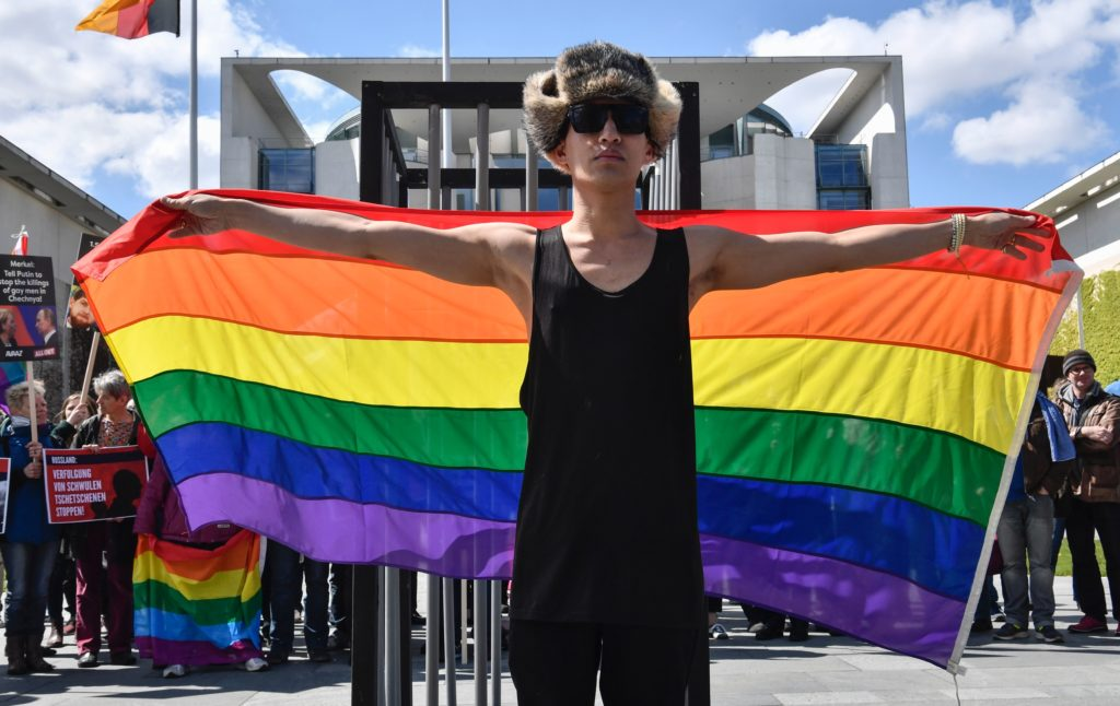An activist displays a rainbow flag in front of the Chancellery in Berlin on April 30, 2017, during a demonstration calling on Russian President to put an end to the Chechnya anti-gay purge.