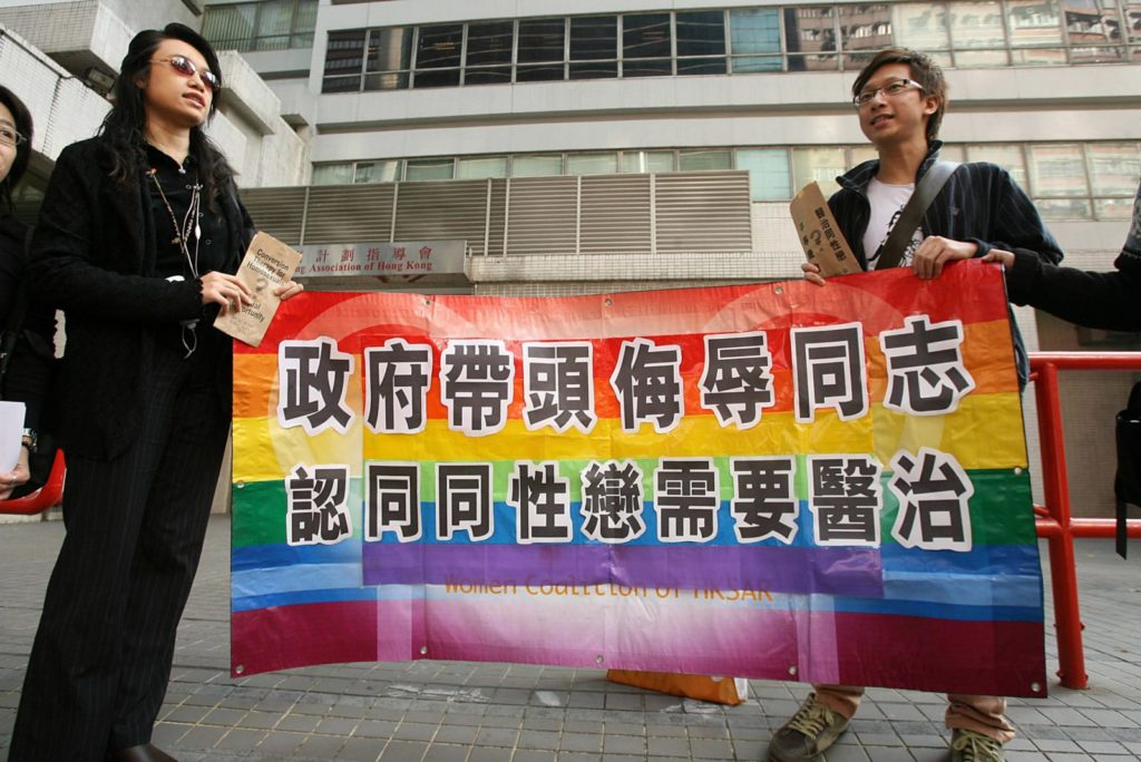 """Hong Kong, CHINA: A gay and homosexual group lead a protest to government offices in Hong Kong 01 December 2006. The group were urging the government to end discrimination to homosexuals with regard to an organisation which promotes conversion therapy for homosexuals. Banner reads"""" Government leads campaign to insult gays and believes they need a cure"""" AFP PHOTO/MIKE CLARKE (Photo credit should read MIKE CLARKE/AFP/Getty Images)"""