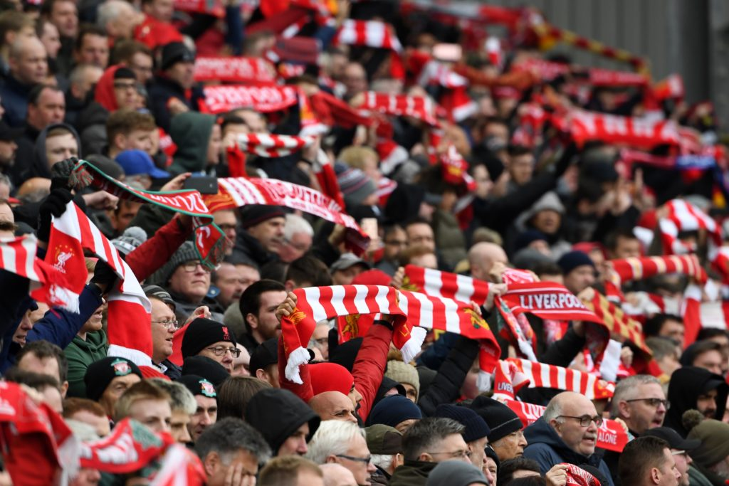 Liverpool supporters hold up their scarves in the crowd ahead of the English Premier League football match between Liverpool and Chelsea at Anfield in Liverpool, north west England on April 14, 2019.