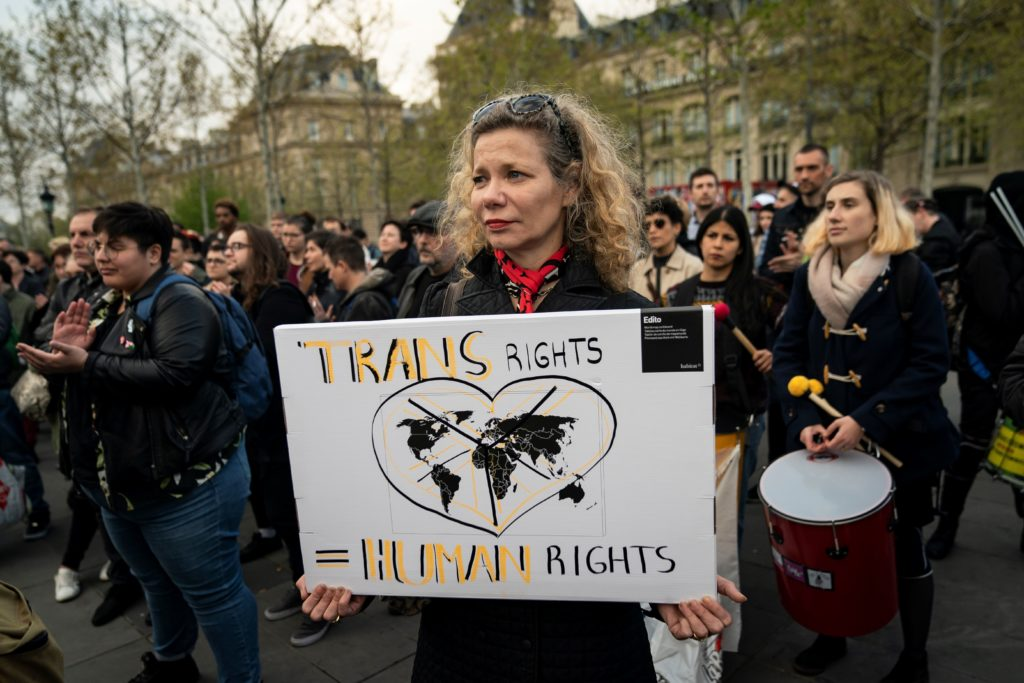"""A woman holding a sign which reads """"trans rights are human rights"""""""