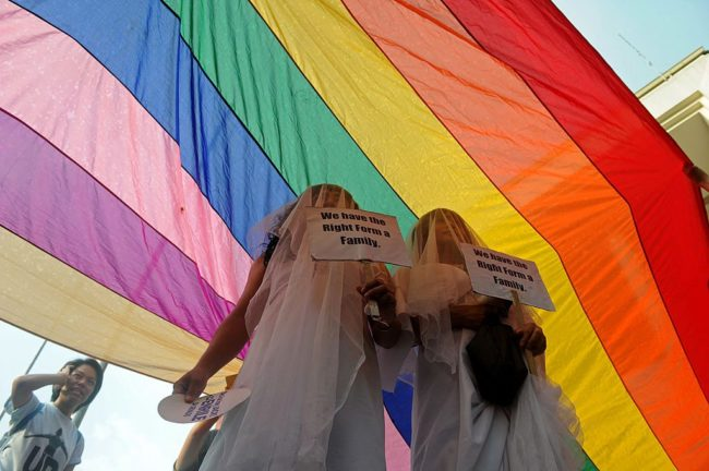 Supporters of same-sex marriage protest in wedding dresses