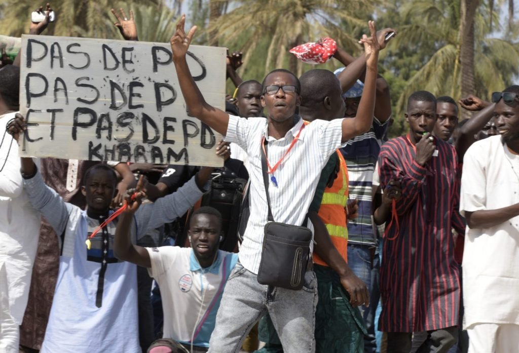 """A protestor gestures on January 22, 2015 in Dakar during a demonstration against homosexuality. Under Senegalese law, anyone convicted of an """"improper or unnatural act with a person of the same sex"""" faces up to five years in jail. The government has repeatedly ruled out legalising homosexuality in the deeply conservative Muslim-majority country. Banner reads """"No fag"""". / AFP / SEYLLOU (Photo credit should read SEYLLOU/AFP/Getty Images)"""