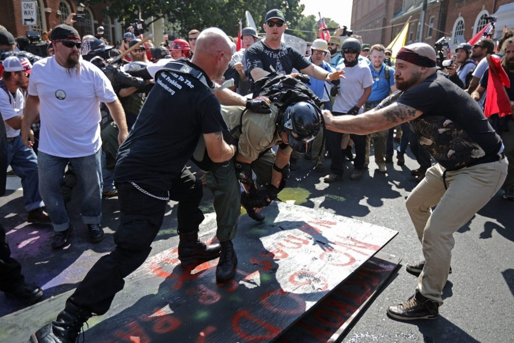 "CHARLOTTESVILLE, VA - AUGUST 12: White nationalists, neo-Nazis, the KKK and members of the ""alt-right"" attack each other as a counter protester (R) intervenes during the melee outside Emancipation Park during the Unite the Right rally August 12, 2017 in Charlottesville, Virginia. After clashes with anti-fascist protesters and police the rally was declared an unlawful gathering and people were forced out of Lee Park, where a statue of Confederate General Robert E. Lee is slated to be removed. (Photo by Chip Somodevilla/Getty Images)"