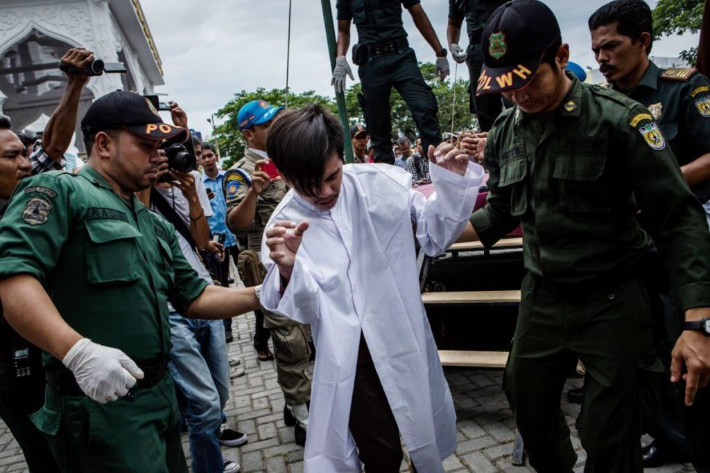 A man in Indonesia is escorted by the Sharia police after get caning in public from an executor known as 'algojo' for having gay sex, which is against Sharia law