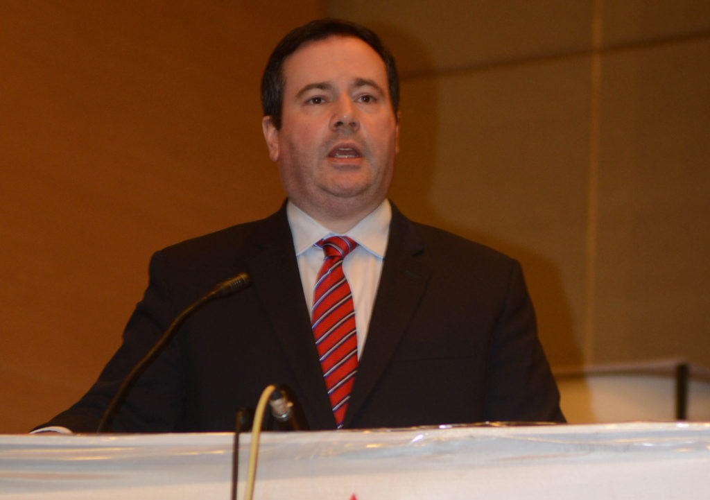 Jason Kenney speaking into a microphone