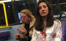 Two women on a bus covered in blood