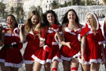 Young women dressed in Santa Claus outfit pose within the traditional Christmas bath on a beach in downtown Nice