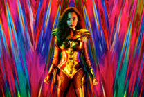 Gal Gadot as Wonder Woman in a gold suit in front of a multicoloured backdrop
