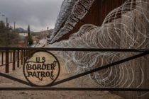 A metal fence marked with the US Border Patrol sign prevents people to get close to the barbed wire covering the US/Mexico border fence
