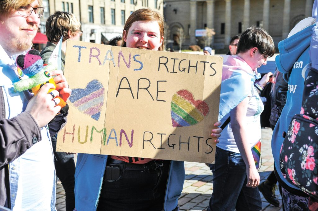A participant is seen holding a placard during the 2019 Trans Pride march in Dundee.