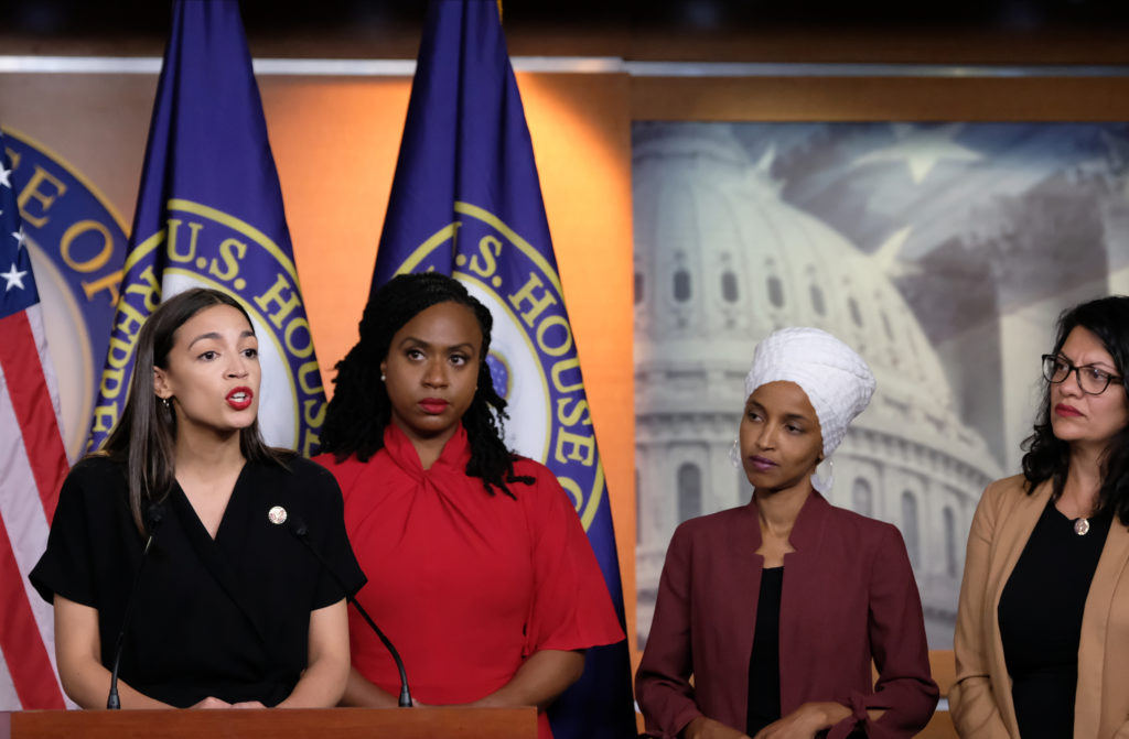 Alexandria Ocasio-Cortez speaks as Ayanna Pressley, Ilhan Omar and Rashida Tlaib stand next to her listening