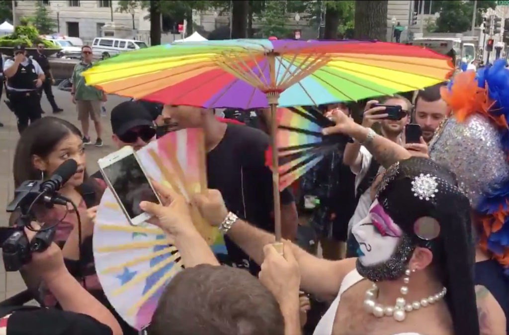 Drag queens in white paint flicking hand fans