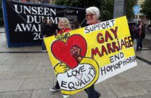 "A woman holding a placard which reads: ""Support gay marriage end homophobia."""