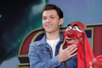 Tom Holland holding a Spider-Man mask
