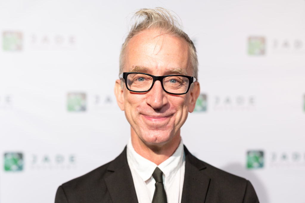 Andy Dick smiling, wearing a suit and black tie