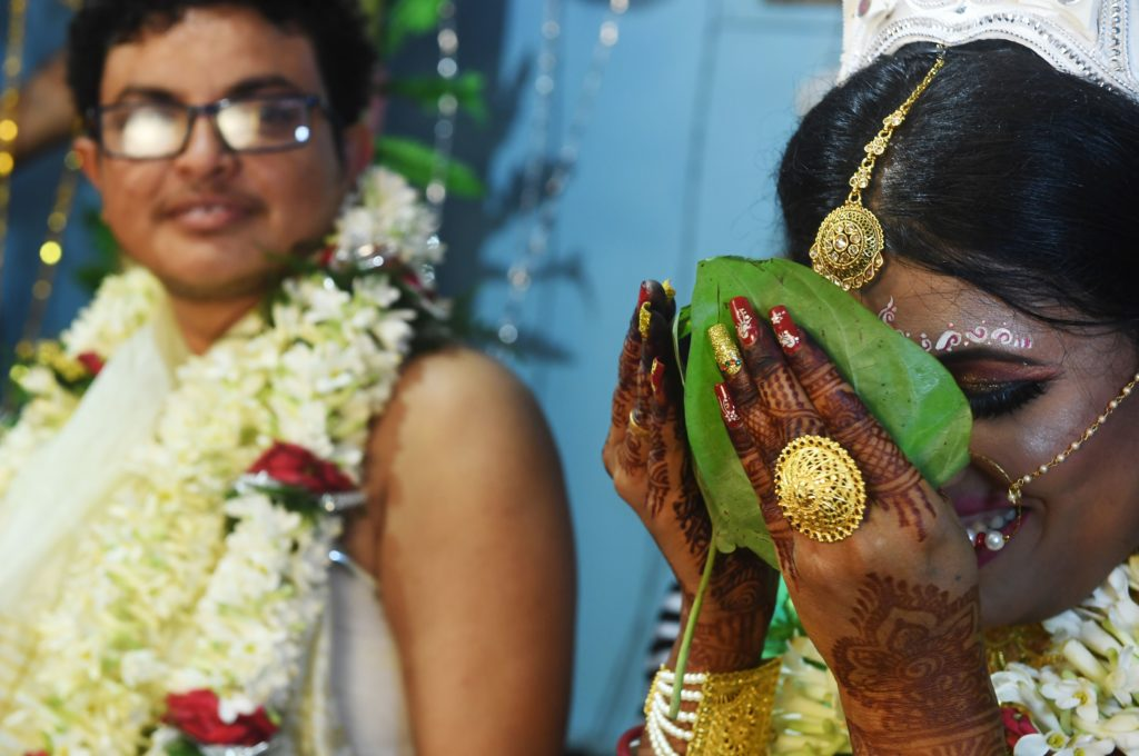 A trans bridge and groom performing marriage rituals, she is holding a leaf to her face as he looks on smiling