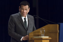 Rodrigo Duterte speaking at a lectern, wearing a black suit and tie
